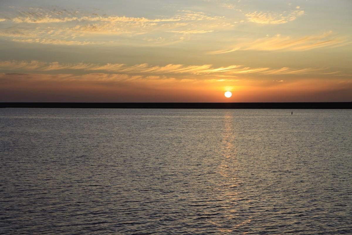 De zon zakt langzaam richting de dijk