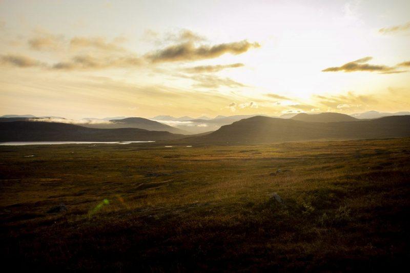 De laatste zonnestralen schijnen over de weidse tundra