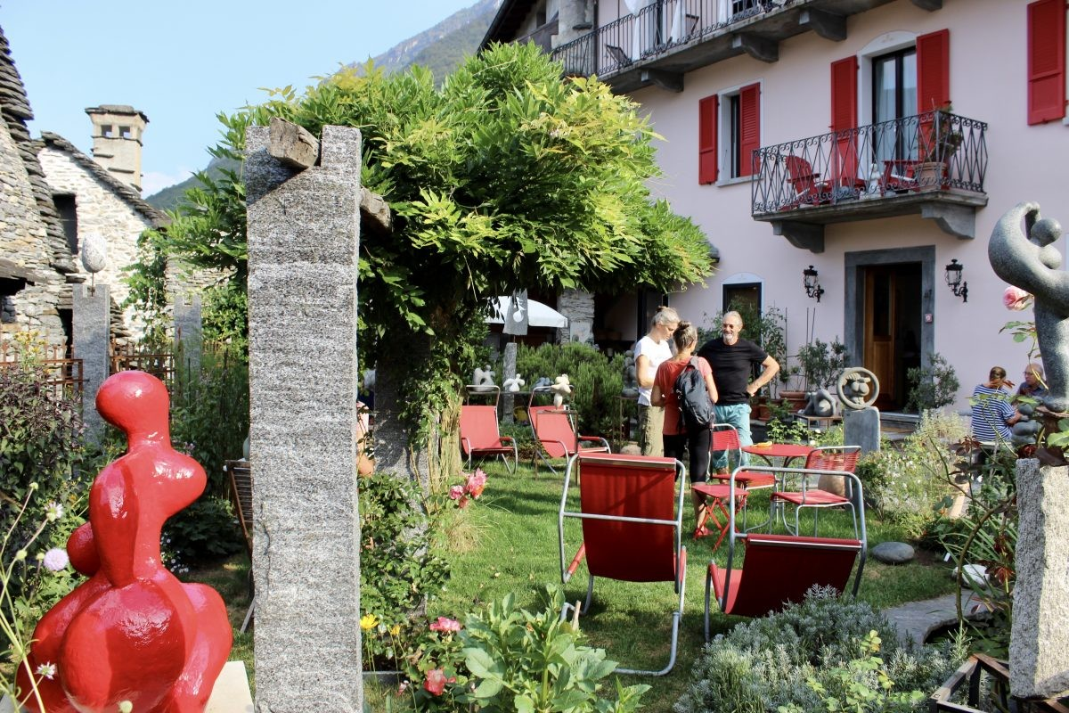 Fausto laat zijn beelden zien in de tuin.