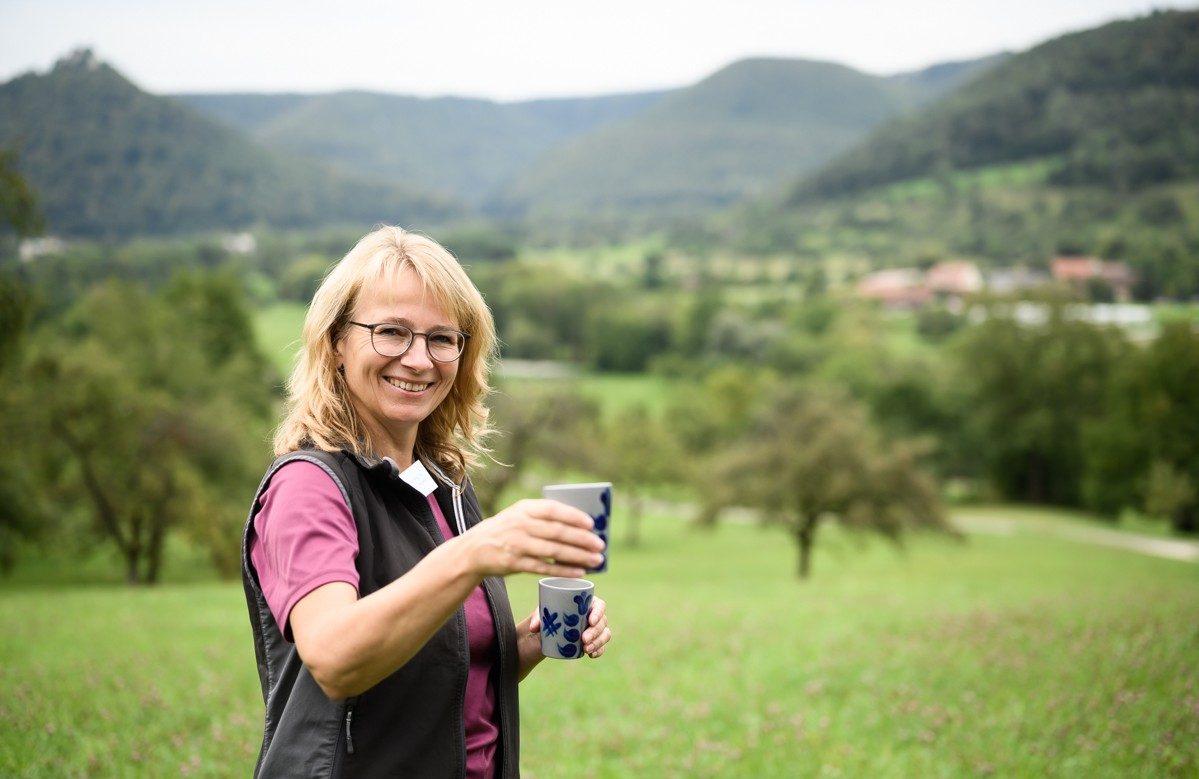 Frau Witzel-Wilhelm laat deelt sap uit. Het zit in bekers die ook typerend zijn voor de streek. Foto: Manja Herrebrugh